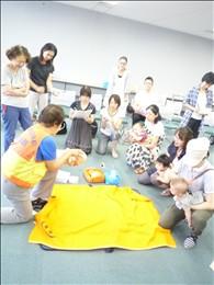 食べ物を喉に詰まらせた場合、子どもはうつぶせにして背中を叩きます。講師は人形で、参加者はご自身の子どもで実習しました。(背中は実際には叩きません)